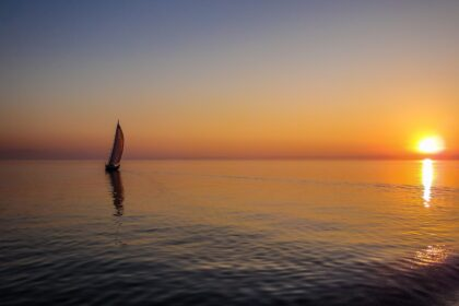 silhouette of sail boat on body of water